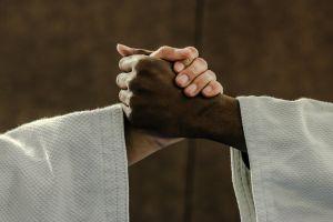 twee elkaar reikende handen in judo-outfit