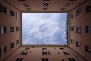 Appartementen in een vierkant gebouwd. Als je naar boven kijkt zie je de lucht.