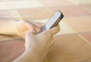 Twee handen houden een smartphone vast.