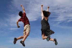 een jongen en meisje springen hoog in de lucht