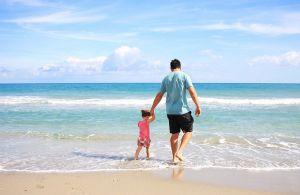 papa en kind aan strand