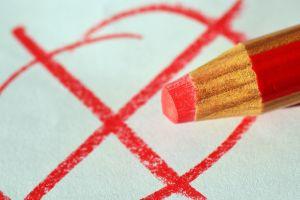 rood potlood dat een rood kruis op papier zet