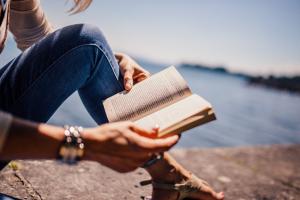 Vrouw leest in een boek. Op de achtergrond zie je een meer.