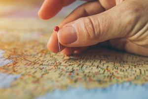 hand prikt een speldenkopje in een landkaart
