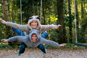 two people are lying on a swing