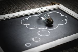 chalkboard on which a thought cloud has been drawn, in which there is a light bulb