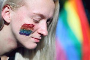 Vrouw met regenboogkleuren op haar gezicht