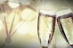 2 champagneglazen die klinken, vuurwerk en een klok op de achtergrond