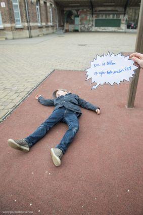 Een kind ligt op de grond terwijl een ander kind een tekstballon vasthoudt