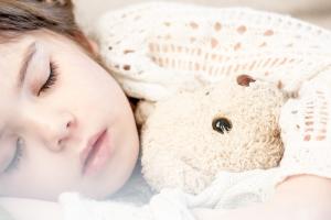 kind slaapt met een knuffelbeer onder de arm