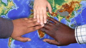Drie handen op een wereldkaart