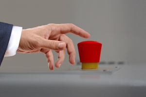 Hand reaching for a red button