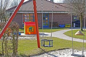 speelplaats met schommel en speelhuisje