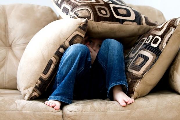 Jongen verbergt zich onder kussens
