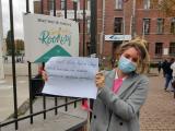 actiefoto leerling met poster aan schoolpoort