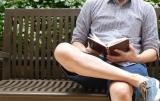 Man leest boek op bank.