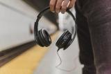 Jongeman wacht op trein met hoofdtelefoon in de hand.