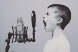 Jongen zingt luidkeels aan microfoon