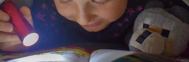 Jongetje leest boekje onder de lakens