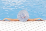 Dame met grote hoed aan zwembad